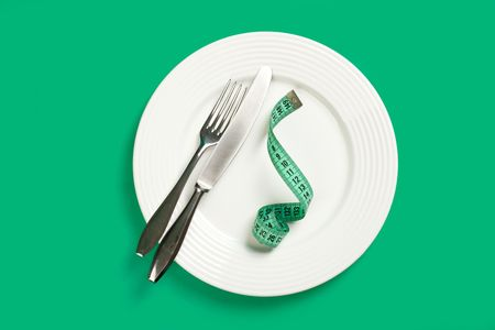 dishes with measuring tape on green background photo