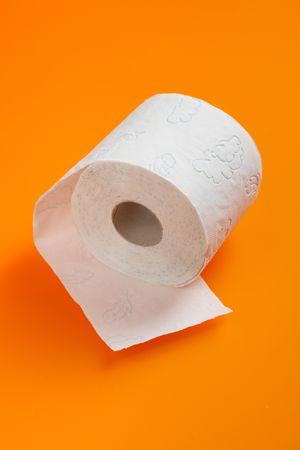 photo shot of toilet paper on orange background photo