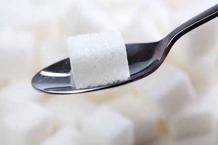 sucrose: the sugar cube on spoon Stock Photo