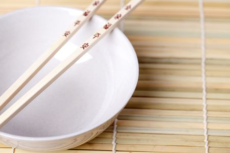 chopsticks and bowl on bamboo placemats photo