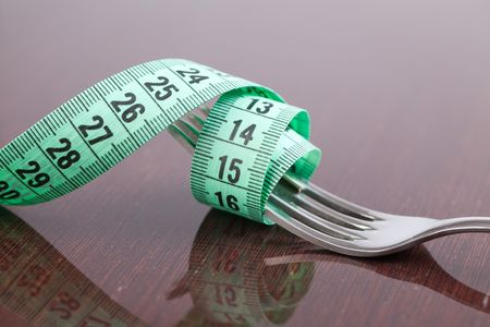 fork with measuring tape on wooden table photo