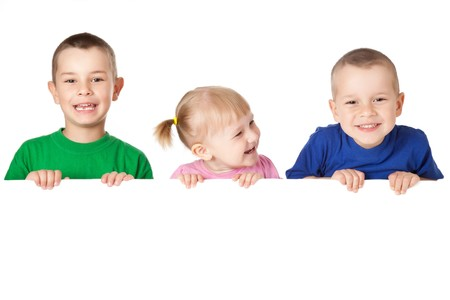 hermanos jugando: disparo de estudio de tres ni�os detr�s de tablero blanco
