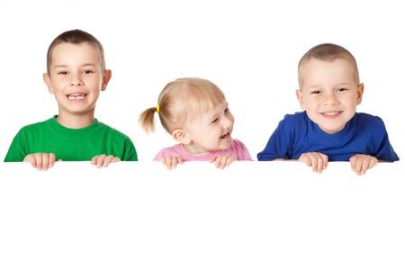 enfants qui rient: Studio grenaille de trois enfants derri�re le jury blanc  Banque d'images