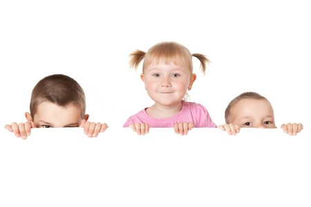 studio shot of three child behind white board photo