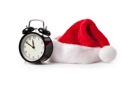 merry time: xmas red hat and alarm clock on white background Stock Photo