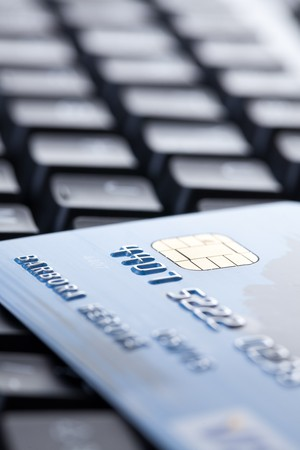 technology transaction: shot of credit card on computer keyboard