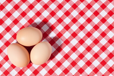 three eggs on picnic tablecloth photo