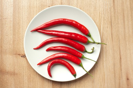 red chili peppers on woodden table photo