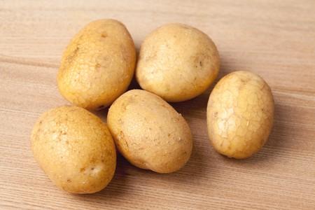 fresh potatoes on wooden table photo