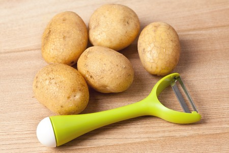 fresh potatoes with vegetable peeler on wooden table photo