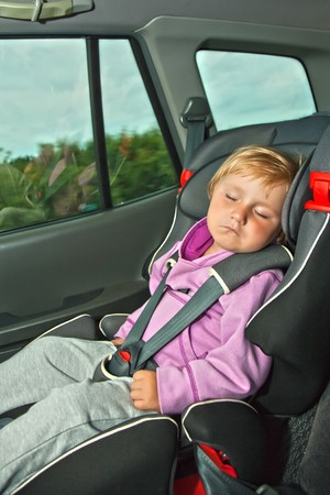 photo shot of sleeping child in car seat  photo