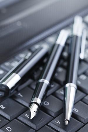 the luxury black pen on computer keyboard photo