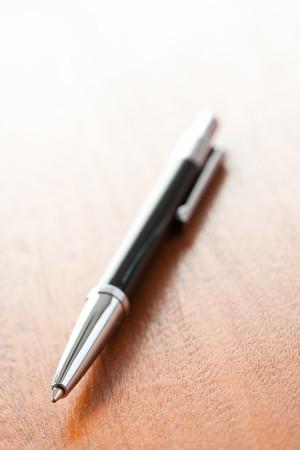 ballpoint pen: the black pen on wooden desk Stock Photo