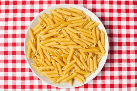 the pasta in plate on picnic tablecloth photo