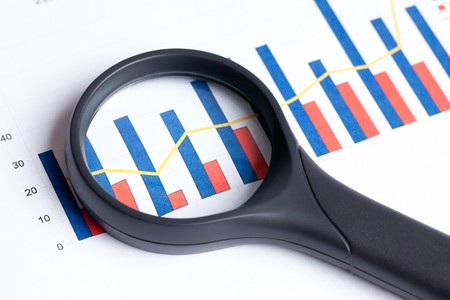 the magnifying glass focusing on business graph photo