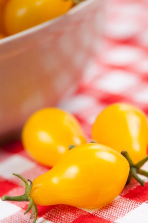 photo shot of yellow tomatoes on picnic tablecloth photo