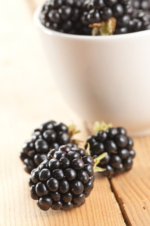 photo shot of blackberries on wooden background photo