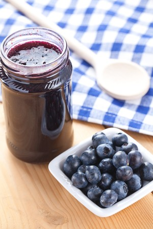 blueberries and jam on wooden table with checkered tablecloth photo