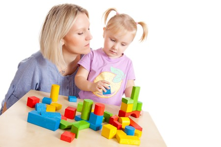 the little girl and her mother playing with toy blocks photo