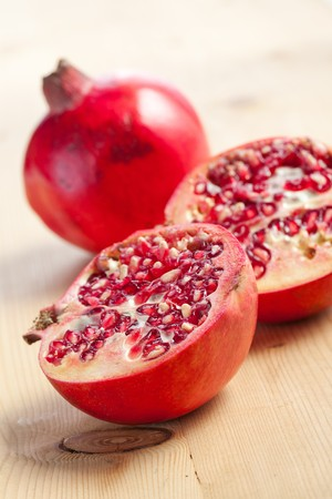 pomegranate juice: sliced pomegranate on wooden table Stock Photo