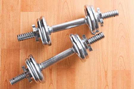 chrome dumbells on wooden floor Stock Photo - 8113401