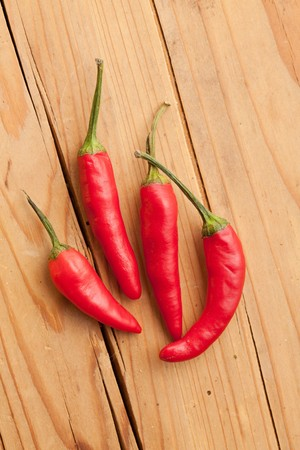 red hot peppers on wooden background photo