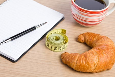 the diet concept . croissant and measuring tape photo