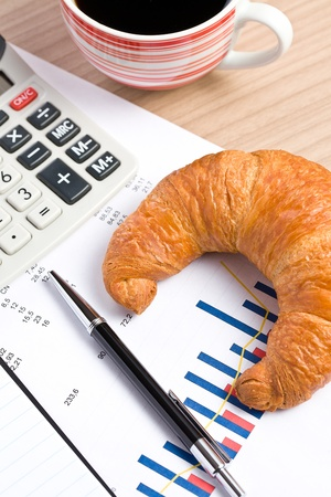 morning in office . croissant and coffee on business graph photo