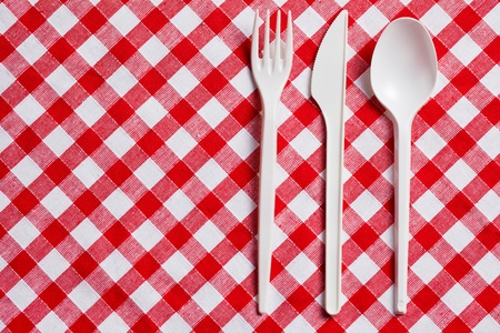 the plastic cutlery on checkered tablecloth photo