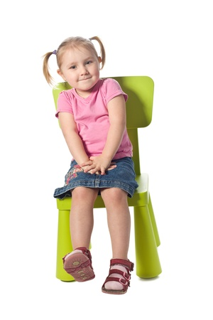 the little child sits on a chair Stockfoto