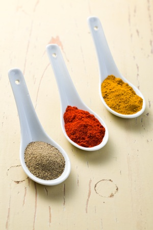 various spicy powder on wooden table photo
