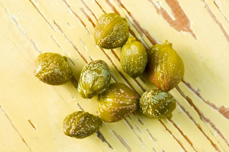 capers: green capers on wooden table Stock Photo