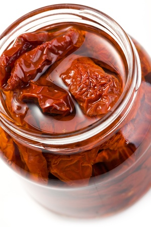dried tomatoes in glass jar on white background photo