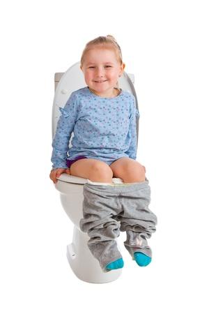 pis: la ni�a est� sentado en el inodoro Foto de archivo