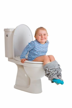 the little girl is sitting on toilet Stock Photo