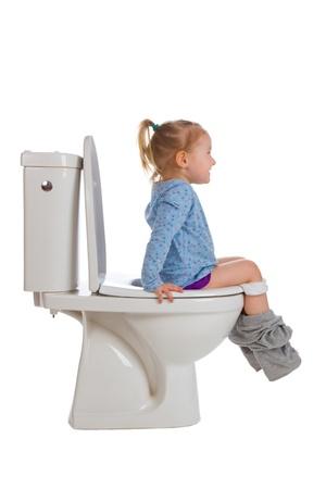 bambini pensierosi: la bambina è seduto sul gabinetto Archivio Fotografico