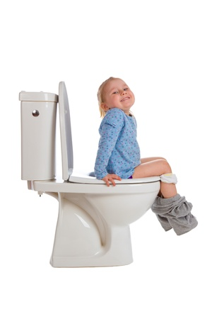 girl toilet: the little girl is sitting on toilet Stock Photo