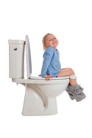 pee pee: the little girl is sitting on toilet Stock Photo