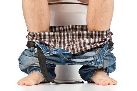 hombre está sentado en el inodoro Foto de archivo