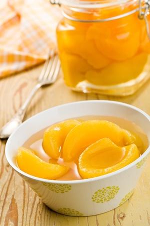 frutta sciroppata: peach in scatola in ciotola in ceramica