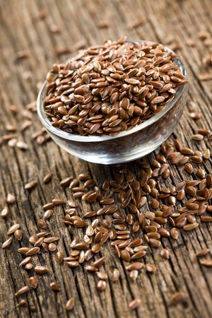 linseed: linseed in bowl on wooden desk Stock Photo
