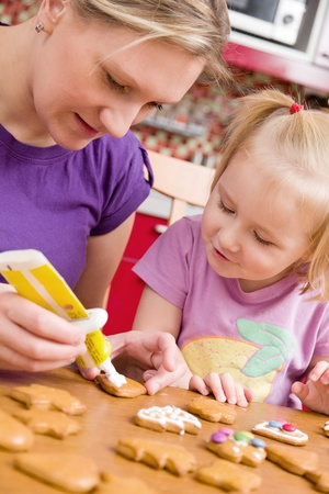 the mother and her daughter decorate ginger bread photo