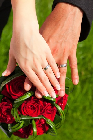 the hands with rings on wedding bouquet photo