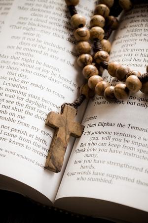 kruzifix: Der hölzerne Rosenkranz auf dem offenen Bibel