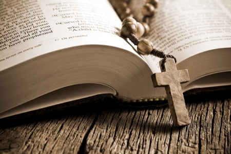 the wooden rosary on the open Bible photo