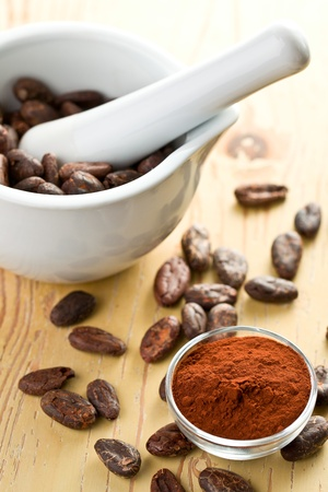 cocoa beans and cocoa powder on wooden table photo