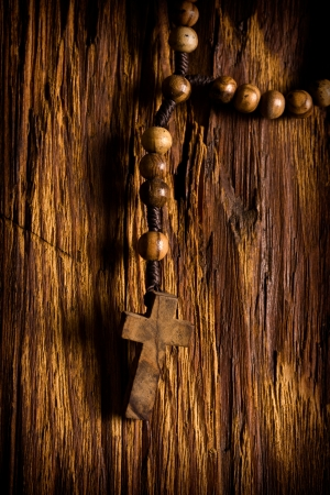 rosary beads: Wooden rosary beads hanging on the old wooden background