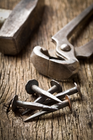 rusty nail: handmade nails with pliers on old background Stock Photo