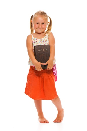 The little girl with holy bible. Studio shot on white background. Stock Photo