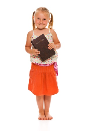 bible background: The little girl with holy bible. Studio shot on white background. Stock Photo